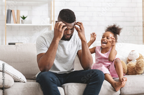 Photo Black father holding his head, tired of bad behaving daughter