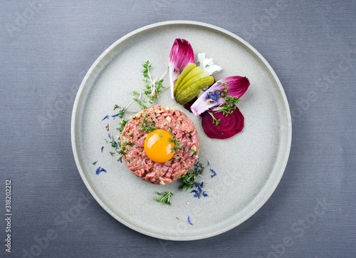 Fotografie, Tablou Gourmet tartar raw from beef fillet with yellow of the egg und vegetable as top