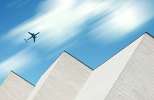 Low Angle View Of Airplane Flying Over Building Against Sky