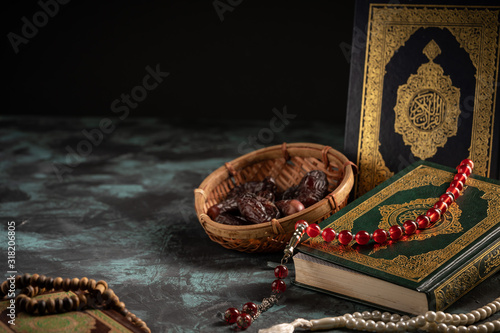 Islamic concept: The holy Quran and Tasbih (rosary beads) on dark background