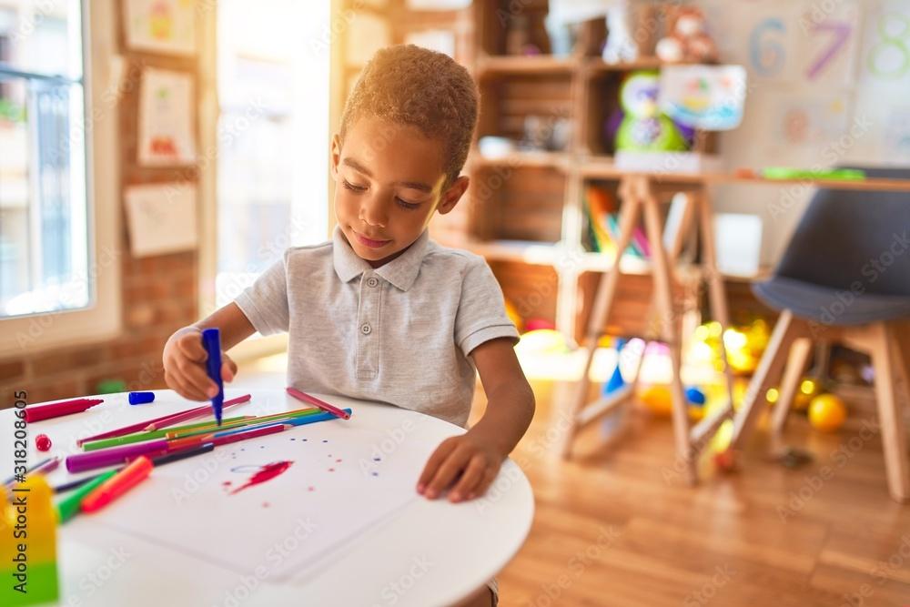 Fototapeta Beautiful african american toddler drawing using paper and marker pen at kindergarten