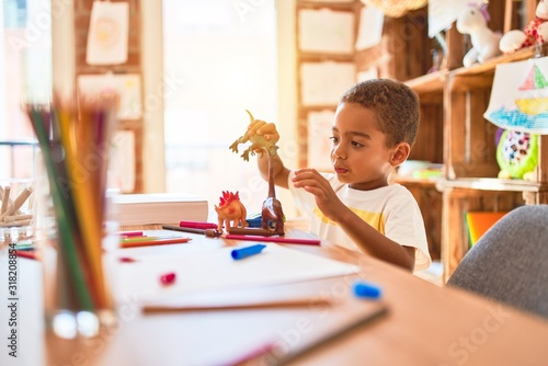 Obraz Beautiful african american toddler playing with dinosaurs toy on desk at kindergarten - fototapety do salonu
