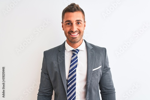 Obraz na plátně Young handsome business man wearing suit and tie over isolated background with a happy and cool smile on face