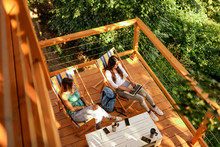 High Angle Image Of Two Young Women Enjoying On A Wooden Cabin Terrace In Forest.