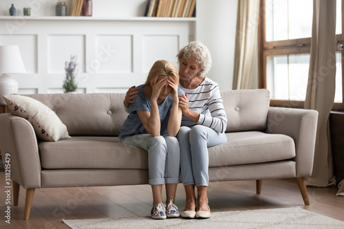 Photo Empathic middle aged mother showing support to grown up daughter.