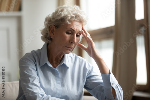 Stressed mature elderly grandmother feeling unwell, sitting alone at home Wallpaper Mural