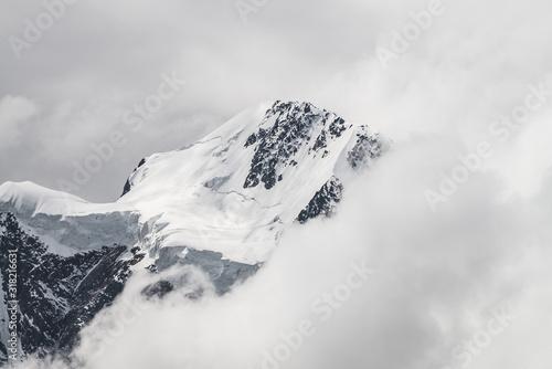 Fototapeta Atmospheric minimalist alpine landscape with massive hanging glacier on snowy mountain peak