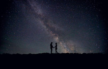 Silhouette Man And Woman Standing On Field Against Star Field