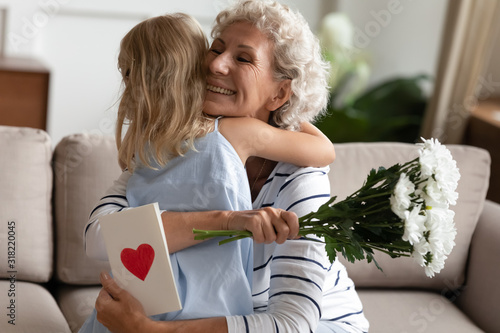 Little child girl congratulating happy elderly senior granny with birthday Wallpaper Mural