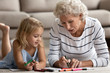 Old senior woman teaching small granddaughter coloring images.