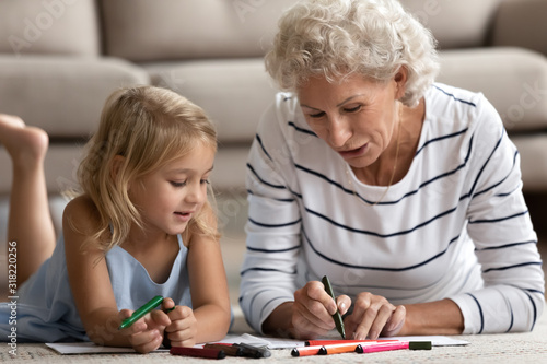 Old senior woman teaching small granddaughter coloring images. Canvas Print