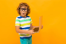 Little Boy With Curly Hair In Colourful T-shirt And Shorts Holds A Laptop Isolated On Yellow Background