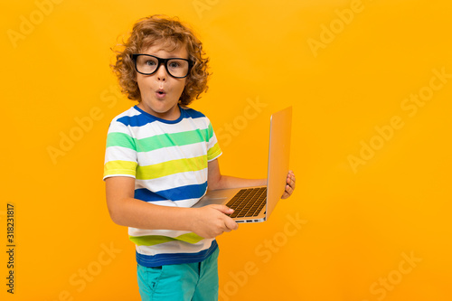 Obraz Little boy with curly hair in colourful t-shirt and shorts holds a laptop isolated on yellow background - fototapety do salonu