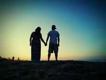 Rear View Of Man And Woman Holding Hands While Standing At Beach