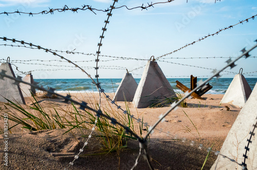 barbed wire and concrete military fence on the beach near the sea in Crimea Canvas Print