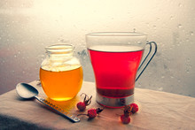 A Jar Of Honey, A Glass Of Tea With A Spoon And Hips Of Wild Rose Standing On Left Side Near The Window Glass With Raindrops.