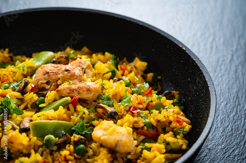 Fotografiet Paella seafood in cooking pan on wooden background