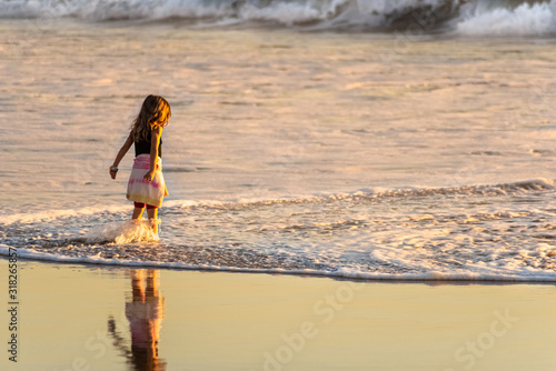 Fototapeta A little girl taking a brave posture and tackling the waves in Malibu Zuma Beach