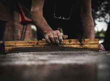 Midsection Of Worker Flattening Cement On Floor At Construction Site