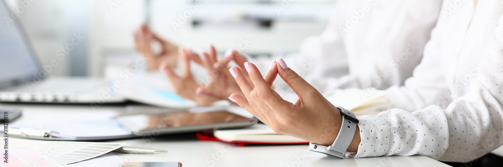 Fototapeta Focus on tender female hands of hardworking businesswoman positioning arms in special relaxing pose at modern workplace with friendly colleagues. Business teamwork concept