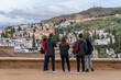 Group of tourists look at the Granada neighborhood of the Albaicin from the Alhambra