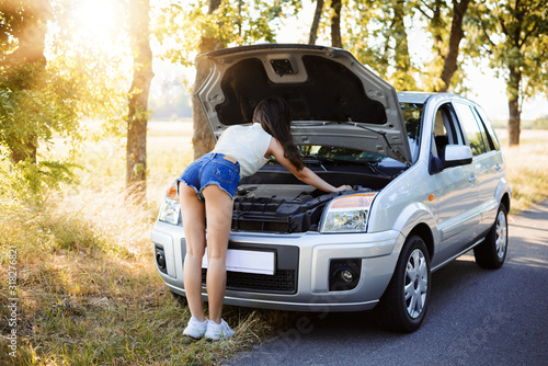 Young attrective girl fixing engine of modern car in the countrisude, leaning ov Canvas Print