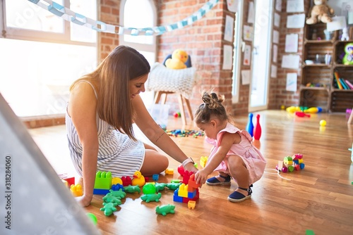 Obraz Young beautiful teacher and toddler sitting on the floor playing with building blocks toy at kindergarten - fototapety do salonu