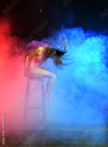 beautiful girl in a pink bathing suit sits on a chair with flying unusual hair against the background of falling water and smoke - 318285494