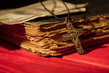 Ornamented Decorative Golden Cross And Old Book Close-up. Christian Religion Items And Money.