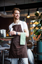 Smiling Industrious Waiter With Napkin Working In Cafe