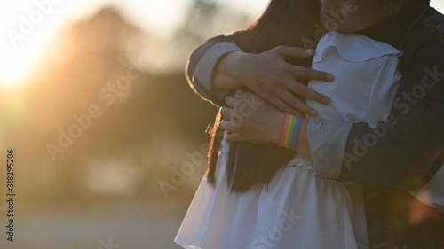 Cropped shot of young LGBT Lesbian couple embracing together at the beautiful park with the blurred sunset light as background Wallpaper Mural