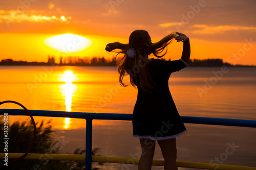 Side view of back light of a woman silhouette breathing deep fresh air at warm sunrise in front of sun Canvas Print