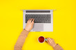 Leinwanddruck Bild - Female hands working on new laptop on bright yellow background Top view, flat lay.