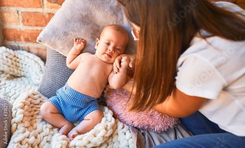 Obraz Young beautifull woman and her baby on the floor over blanket at home. Newborn and mother relaxing and resting comfortable - fototapety do salonu