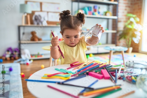 Beautiful toddler standing holding colored pencils at kindergarten Canvas Print
