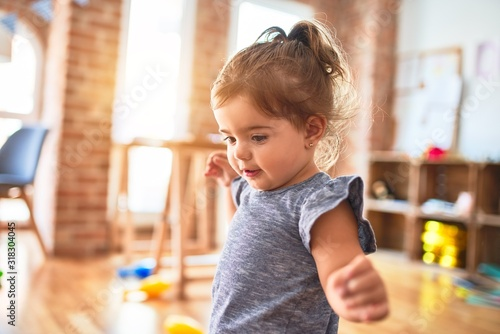 Obraz Beautiful toddler standing around lots of toys at kindergarten - fototapety do salonu