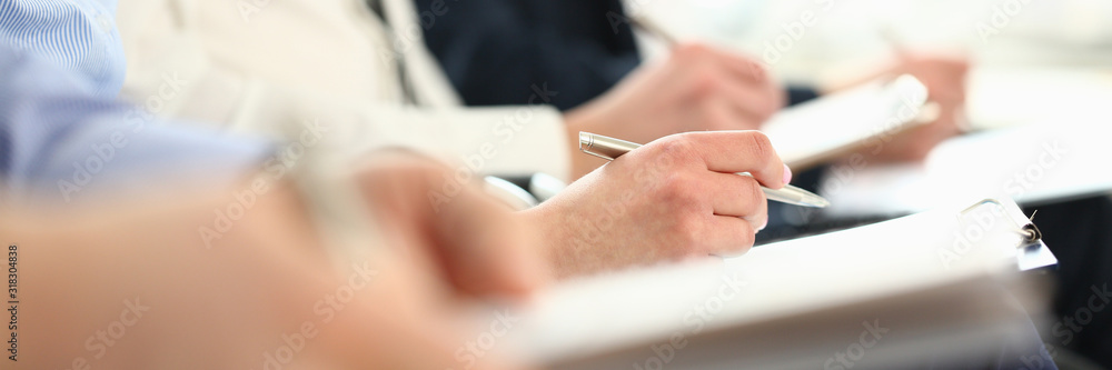 Fototapeta Focus on male hands taking notes at business seminar. Managers sitting together in modern conference room. Company meeting concept. Blurred background