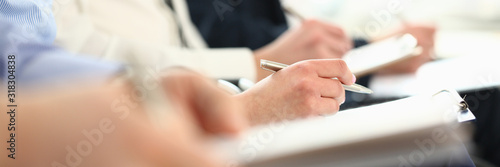 Fototapeta Focus on male hands taking notes at business seminar. Managers sitting together in modern conference room. Company meeting concept. Blurred background obraz