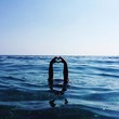 Hands Forming Heart Shape At Blue Sea