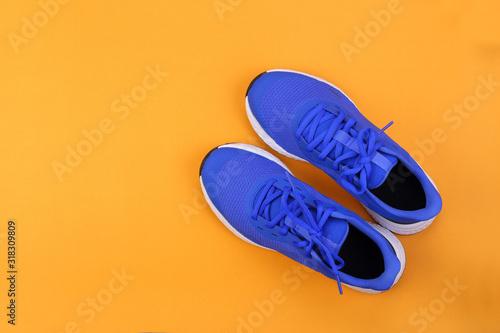 Obraz Top view blue running shoes on orange pastel background - fototapety do salonu