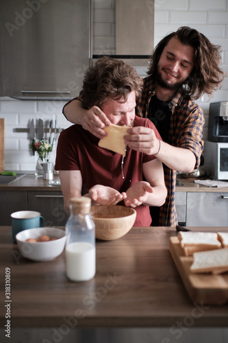 Gay couple goofying at the kitchen while making breakfast Wallpaper Mural