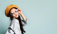 Little Asian Kid In Sunglasses, Oversized Shirt Dress, Brown Beret, Boots. She Kissing You, Posing On Blue Background. Full Length