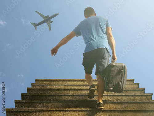A guy with a suitcase runs up the stairs in the rays of sunlight against the background of a blue sky with a passenger plane Canvas Print