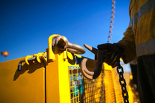Close Up Industrial Rigger High Risk Worker Hand Wearing Safety Heavy Duty Glove And Clipping A Crane Hook Into Yellow Crane Lifting Gate Prior Lifting In Construction Site Perth City, Australia