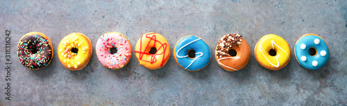 Various colourful donuts in a row on rustical background фототапет