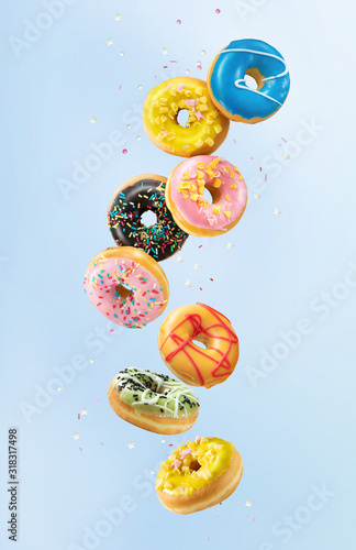Various colorful doughnuts in motion on blue background