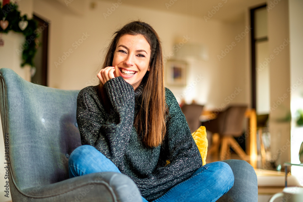 Fototapeta Happy woman relaxing at home in the armchair