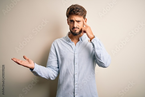 Valokuva Young handsome man with beard wearing striped shirt standing over white background confused and annoyed with open palm showing copy space and pointing finger to forehead