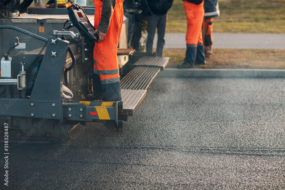 Fototapeta Asphalt paving. Paver machine and road roller. New road construction.