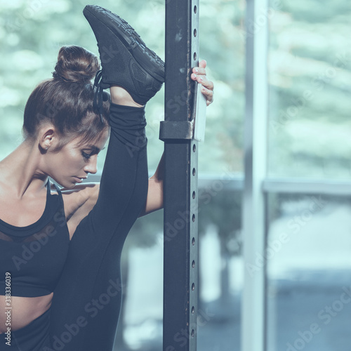 Portrait of young atrractive woman doing split in gym, image with cold vintage t Wallpaper Mural